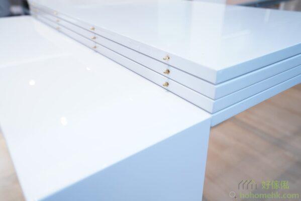 4塊枱面板推疊地放在伸縮餐桌的軌導上