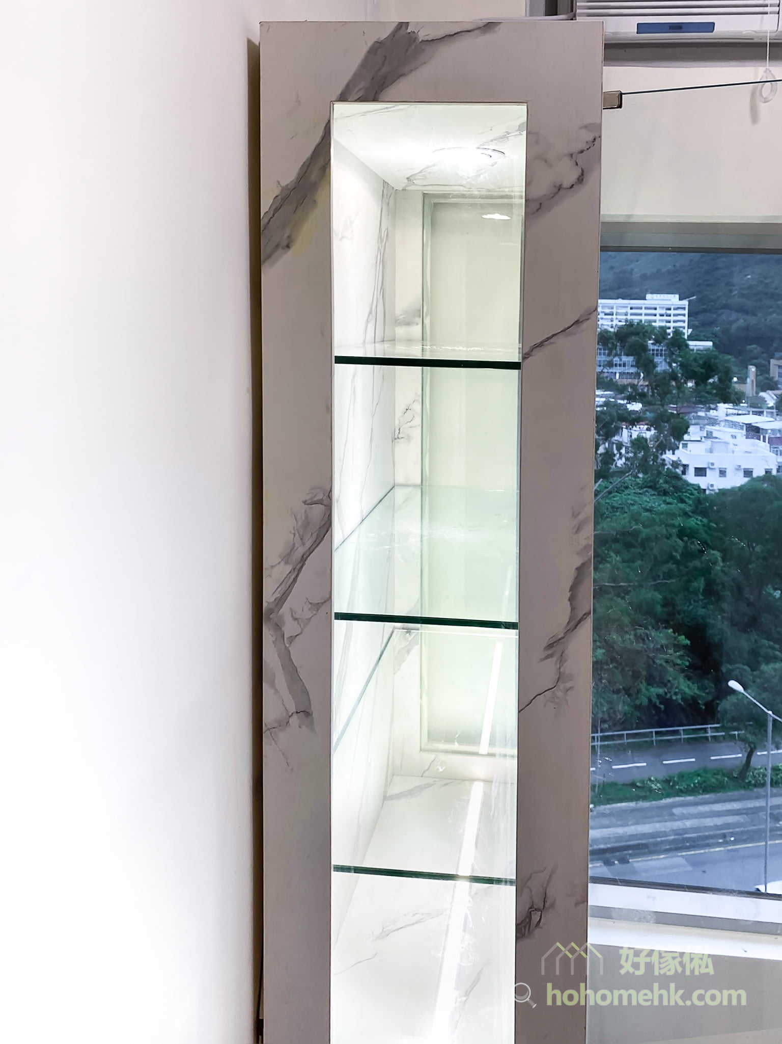 客廳的大理石紋飾物櫃, 櫃身兩側採用玻璃面, 多角度展示收藏品