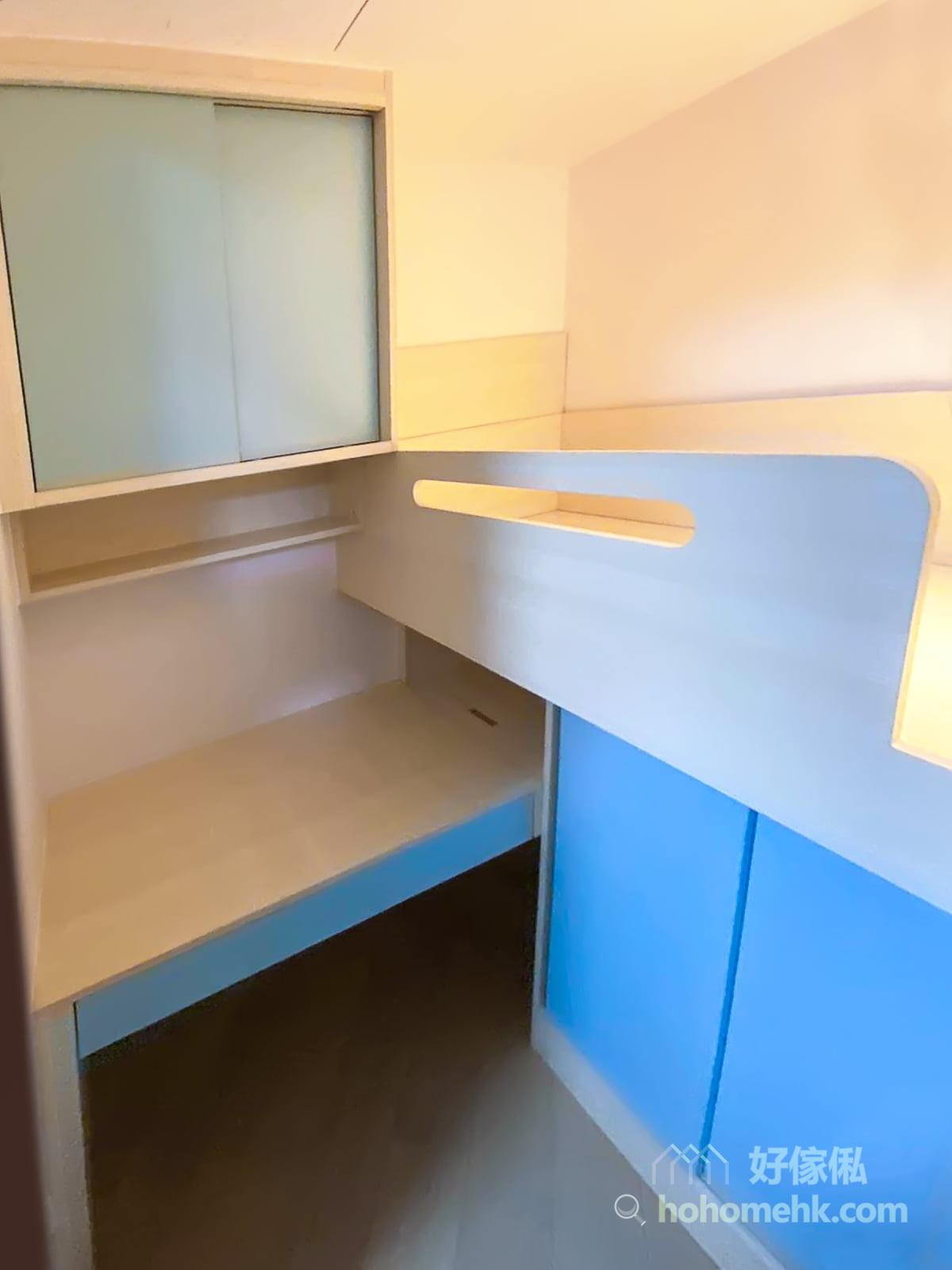 書枱有櫃桶擺放零碎雜物,碌架層下的空間則造了上翻式揭板,一點也不浪費儲物的空間。  書枱上方有趟門吊櫃,跟衣櫃同一式樣,統一整體風格,又為書枱區域提供龐大的儲物