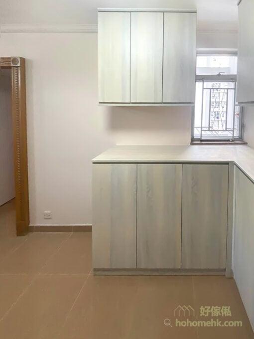 吊櫃部份不做滿整個L形牆面,而是選擇分成兩組獨立吊櫃,讓窗戶外的光線可以引進室內,加強室內的空間感