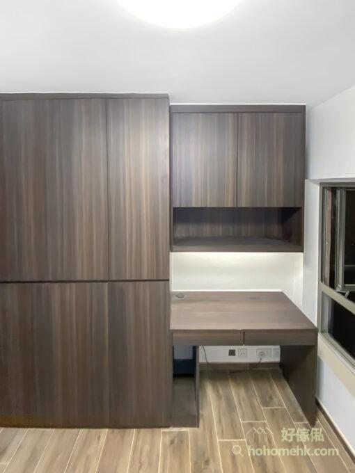 深胡桃木色的書枱採用分段式的吊櫃配書枱,讓更多的牆面可以露出來,減低壓迫感。而書枱腳以輕巧為主,重色調卻輕量化的處理手法,展現出了簡約中必要的線條張力