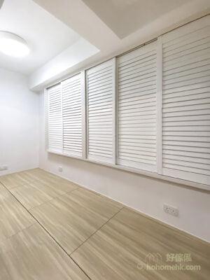 造型俐落的白色木百葉窗簾,能夠完全將不太漂亮的鋁窗框給隔絕在外,再配上純白牆身以及淺木色地台,讓空間瀰漫著一股明淨透亮、寧靜通透之美