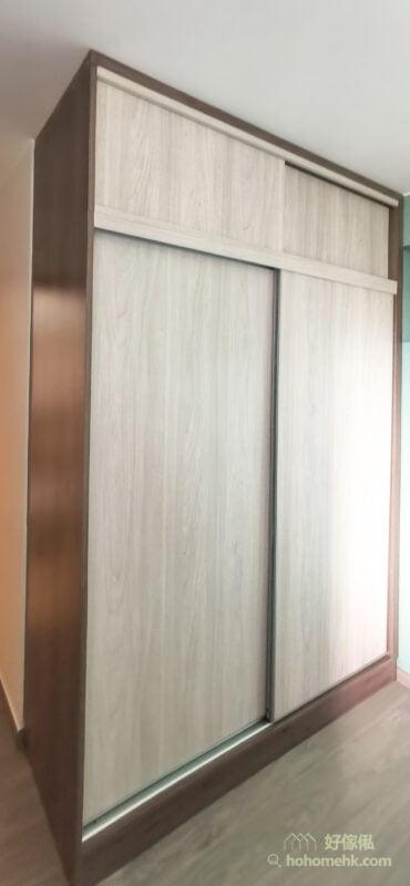 案例中選用一深一淺的拼色配搭,輕易就營造出層次感,深色板材做外殼,視覺上可以令衣櫃有縮小的感覺