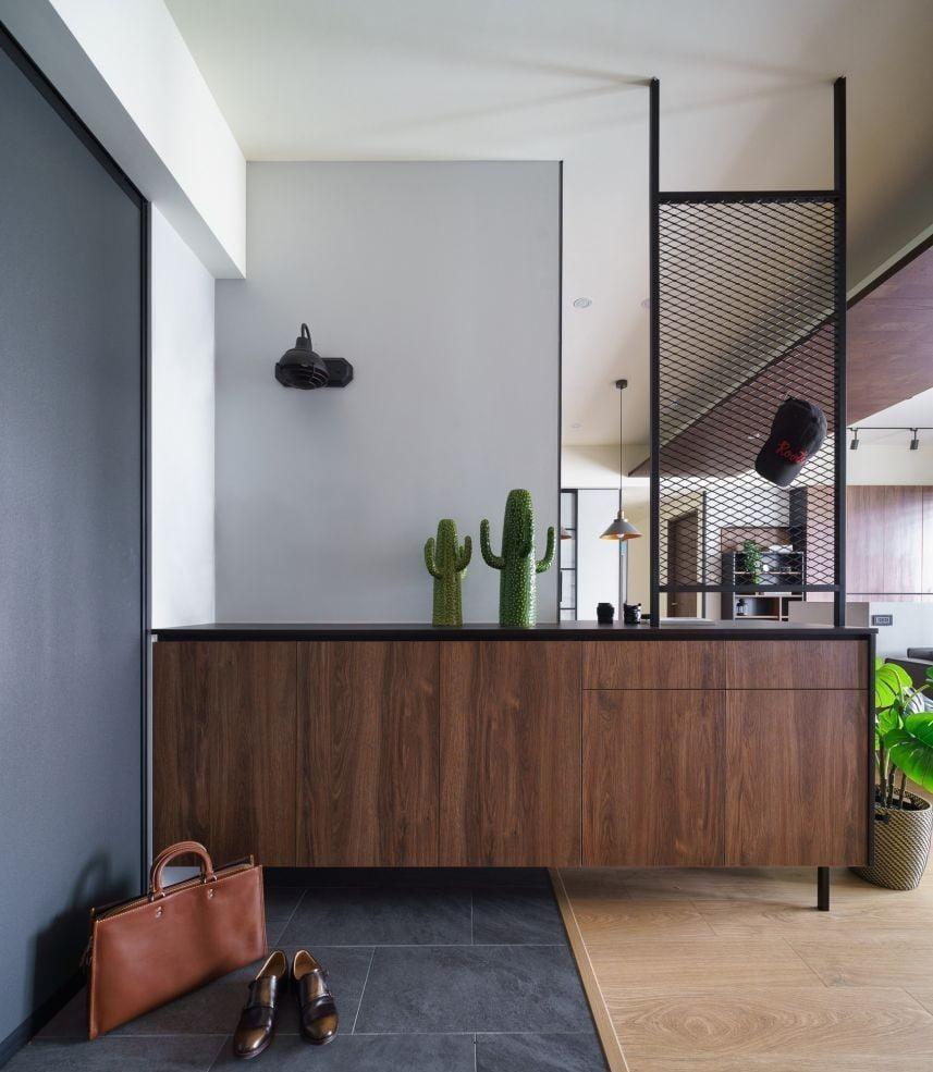 藉由地板不同材質的區隔,將玄關與客廳分開,隔絕室外的紛擾吵雜與灰塵,為室內空間營造溫馨感