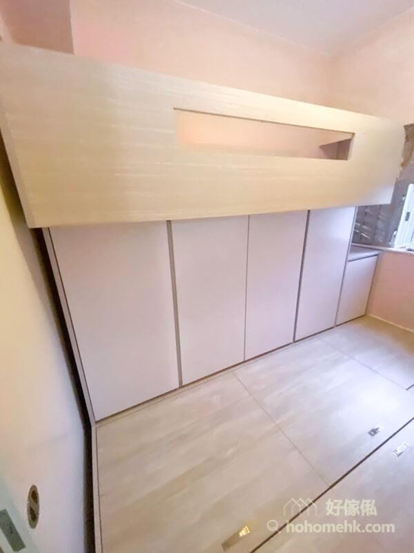 碌架床放在房間的長邊,上層是睡床,下層則是一整排的衣櫃,純白而統一的衣櫃門,垂直的門板令視覺伸延,讓睡房的空間感倍增